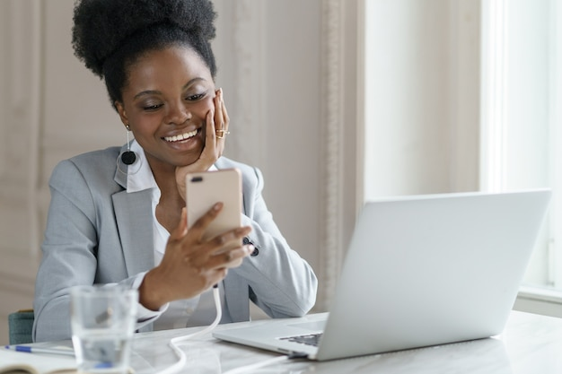 Smiling afro woman take a break chatting with friend about weekend in social media sitting at office
