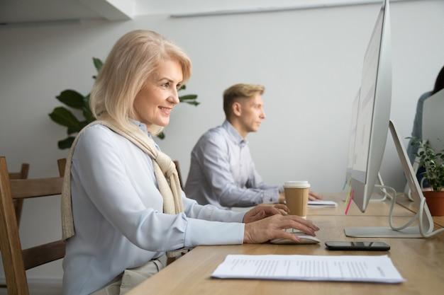 Усмехаясь постаретая коммерсантка используя компьютер работая онлайн в офисе коворкинг
