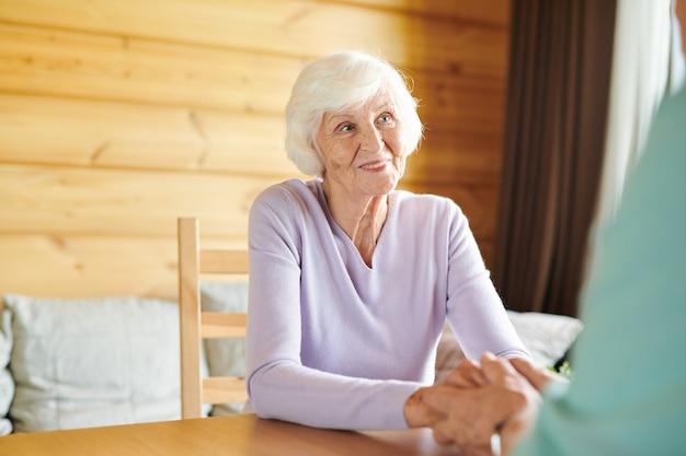 Улыбающаяся пожилая случайная женщина смотрит на мужа во время разговора за столом в гостиной их загородного дома