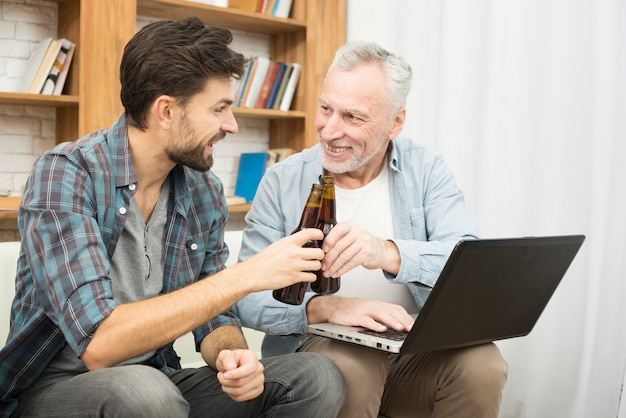 Smiling aged man and young guy clanging bottles and using laptop on sofa