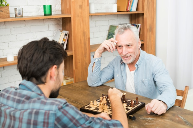 Smiling aged man and young guy playing chess at table near bookshelves