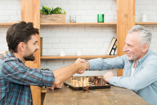 Smiling aged man and young guy shaking hands at table with chess board