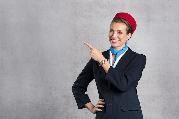 Smiling air hostess showing