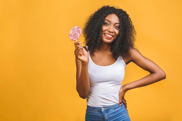 Улыбающаяся американская африканская девушка держит леденец на палочке