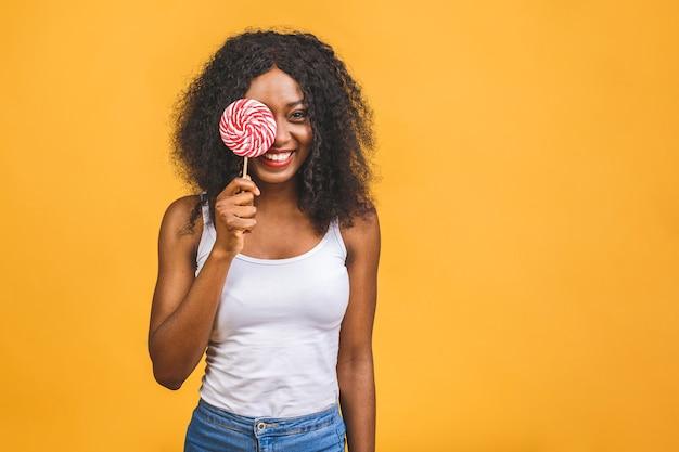 キャンディーロリポップを保持している笑顔のアメリカのアフリカの女の子