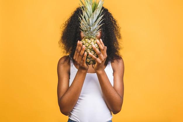 パイナップルを保持している笑顔のアメリカのアフリカの女性