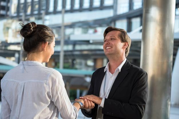 공식적인 유니폼을 입은 웃고 있는 미국 사업가는 도시 도시에서 비즈니스 프로젝트 토론을 하기 전에 사업가와 악수를 나누며 인사를 나누었습니다.