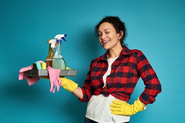 手と腰にクリーニング製品とトレイで青でポーズをとって笑顔のアメリカ人女性。