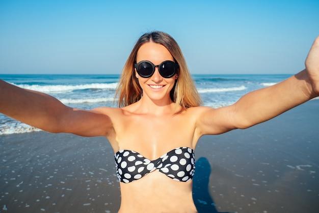 Улыбающаяся и красивая женщина делает селфи в отпуске.