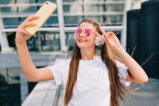 Улыбающаяся и танцующая молодая женщина делает селфи со своим смартфоном и слушает музыку в наушниках