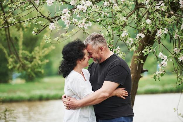 笑顔で抱きしめる。屋外で素敵な週末を楽しんでいる陽気なカップル。良い春の天気