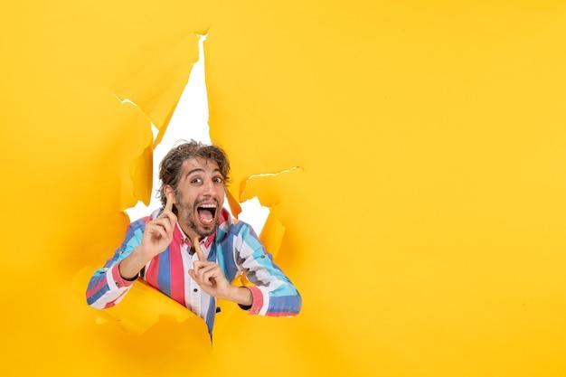 引き裂かれた黄色の紙の穴の背景に笑顔と感情的な満足の若い男のポーズ