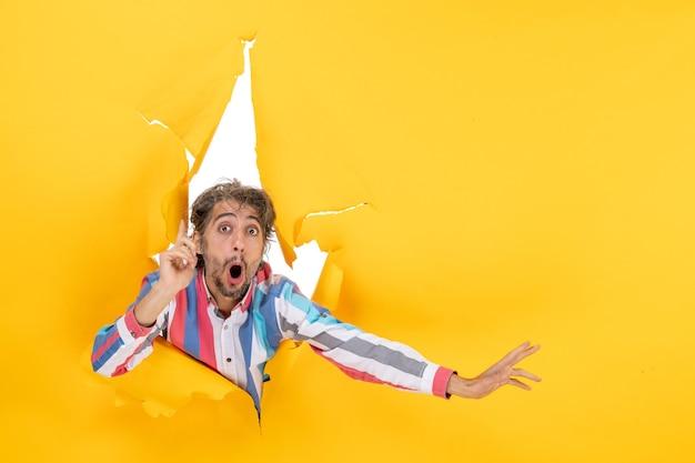 웃고 감정적인 젊은이는 놀란 표정으로 가리키는 찢어진 노란 종이 구멍 배경에서 포즈를 취합니다.