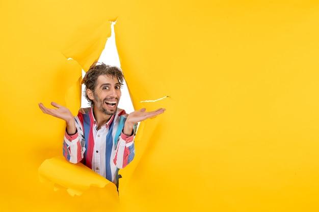 Улыбающийся и эмоциональный молодой человек позирует на фоне рваной желтой бумажной дыры