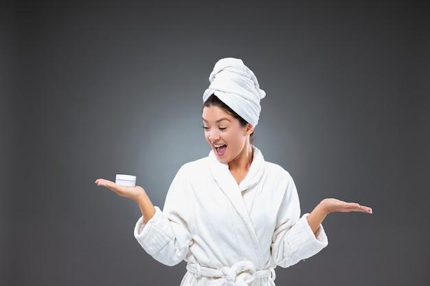 Улыбающаяся и возбужденная милая женщина в халате и полотенце, обернутом вокруг головы, держит крем в руке
