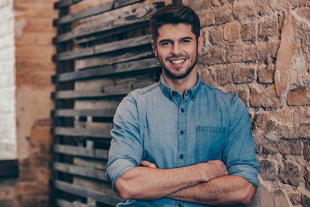 Улыбающийся и красивый. красивый молодой человек, скрестив руки и глядя в камеру с улыбкой, стоя у кирпичной стены