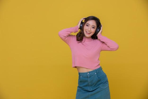 音楽を聴いて楽しんでいるワイヤレスヘッドフォンを着て笑顔で幸せな陽気な美しいアジアの女性