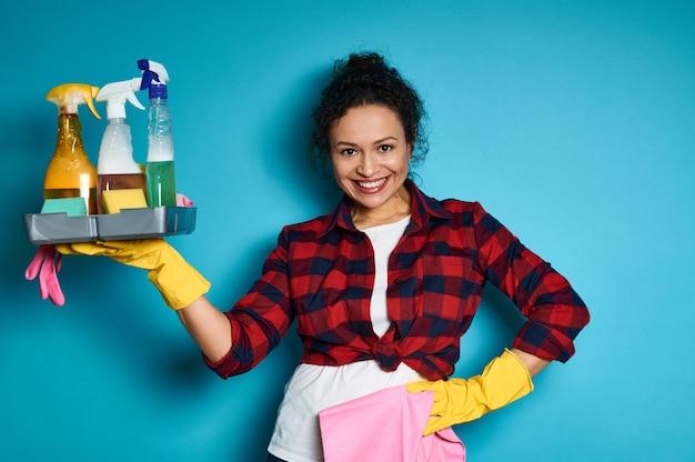 手に化学洗浄剤でいっぱいのトレイで腕を上げる笑顔と幸せなラテンアメリカの女性