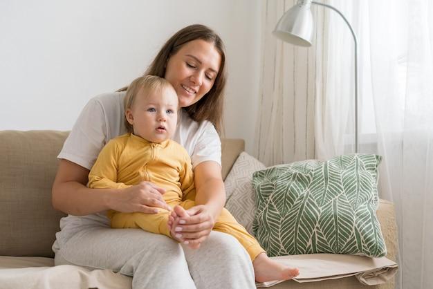 밝은 거실에서 사랑스러운 아기와 함께 소파에 앉아 웃고 있는 행복한 여성