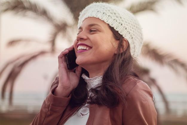 通りでスマートフォンを使用して笑顔と幸せな女