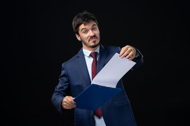 Улыбающийся и счастливый молодой человек в костюме, держащий документы и проверяющий статистику в нем на изолированной темной стене
