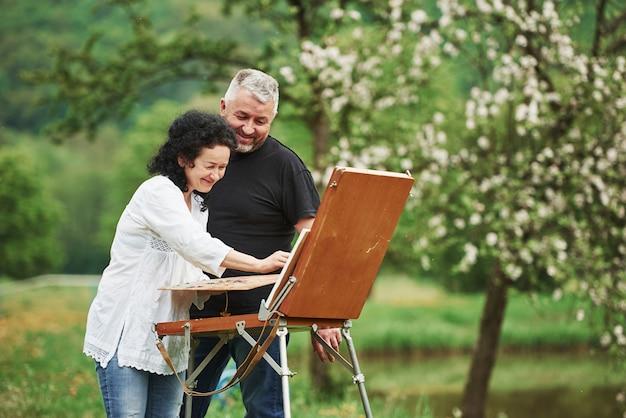 Улыбается и веселится. пожилая пара отдыхает и вместе работает над краской в парке