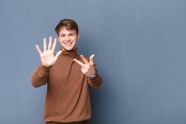 Улыбается и выглядит дружелюбно, показывая номер восемь или восьмой с рукой вперед, считая вниз