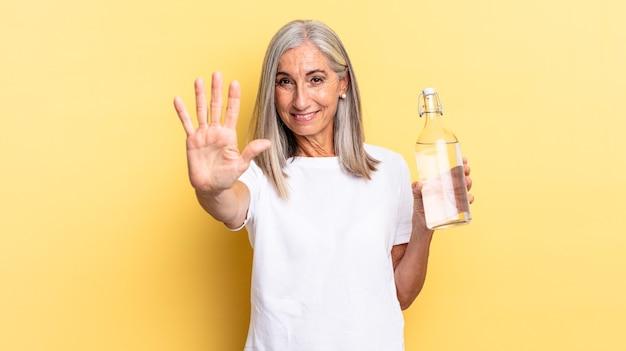 Улыбается и выглядит дружелюбно, показывает пятый или пятый номер рукой вперед, ведет обратный отсчет и держит бутылку с водой.