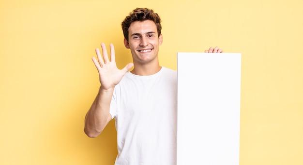 Улыбается и выглядит дружелюбно, показывает пятый или пятый номер рукой вперед и ведет обратный отсчет. концепция пустого холста