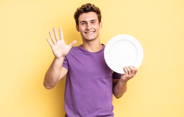Улыбается и выглядит дружелюбно, показывает пятый или пятый номер рукой вперед и ведет обратный отсчет. концепция пустой тарелки