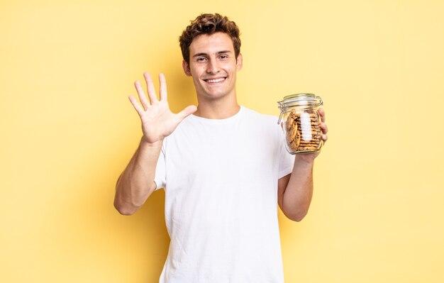 Улыбается и выглядит дружелюбно, показывает пятый или пятый номер рукой вперед и ведет обратный отсчет. концепция домашнего печенья