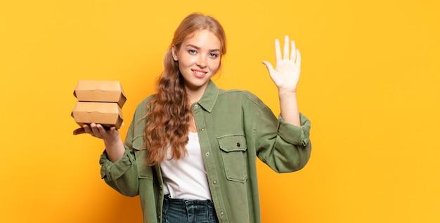 笑顔でフレンドリーに見え、前に手を出して5番または5番を示しています Premium写真