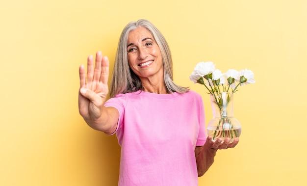 Улыбающийся и дружелюбный, показывающий четвертый или четвертый номер рукой вперед, обратный отсчет в руках с декоративными цветами.