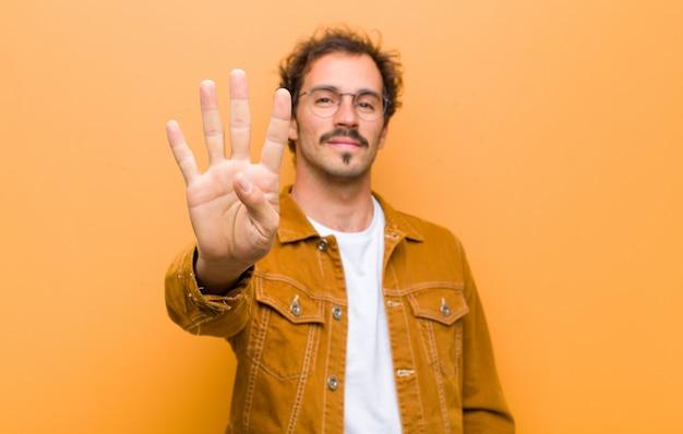 Улыбается и выглядит дружелюбно, показывая номер четыре или четвертый с рукой вперед, считая вниз