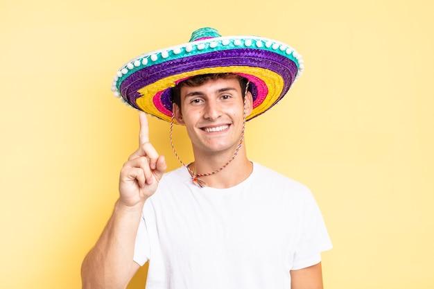 笑顔で親しみやすく、前に手を出してナンバーワンまたはファーストを示し、カウントダウンします。メキシコの帽子の概念