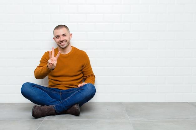 笑顔で親しみやすく、3番目または3番目を手で前にしてカウントダウン