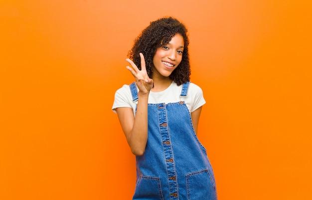 笑顔でフレンドリーに見える、3番目または3番目を手で前にしてカウントダウン