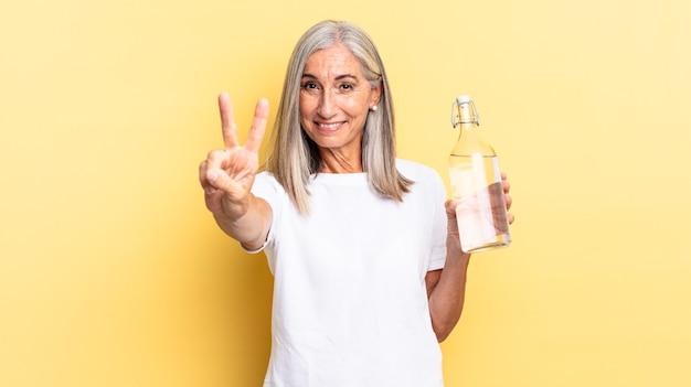 Улыбается и выглядит дружелюбно, показывает цифру два или секунду рукой вперед, ведет обратный отсчет и держит бутылку с водой