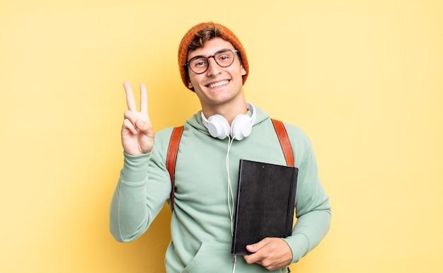 Улыбается и выглядит дружелюбно, показывает цифру два или секунду рукой вперед, ведет обратный отсчет. студенческая концепция