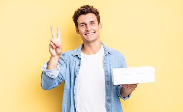미소를 지으며 친근하게 보이고 손을 앞으로 내밀고 숫자 2 또는 2를 표시하고 카운트다운합니다. 흰색 상자 개념