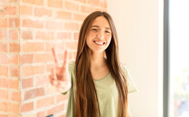 Улыбается и выглядит счастливым, беззаботным и позитивным, одной рукой показывает победу или мир