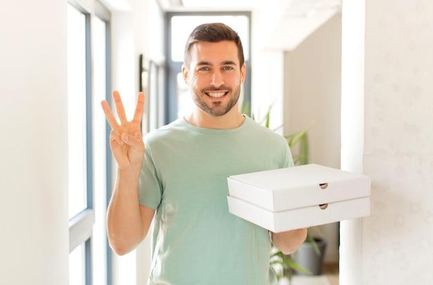 Улыбается и дружелюбно смотрит на человека, показывает цифру три или треть рукой вперед и ведет обратный отсчет