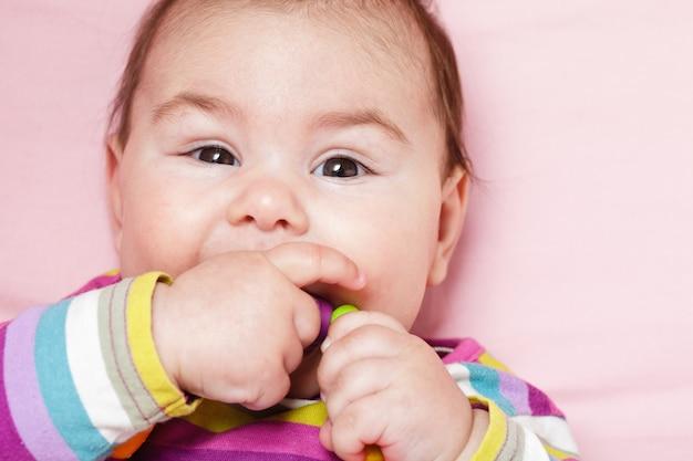 笑顔と歯が生えるリングで赤ちゃんを遊んでいます。クローズアップの顔。
