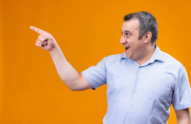 Улыбающийся и позитивный мужчина среднего возраста в синей рубашке с вертикальной полосой, указывая указательным пальцем в верхний правый угол, стоя на оранжевом фоне
