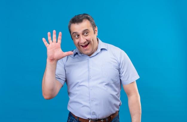 青色の背景にハイタッチ5ジェスチャーを与える青いシャツを着て笑顔と肯定的な中年男