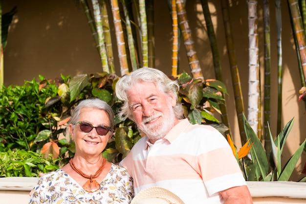 열대 정원의 여름 휴가 배경에서 즐겁게 웃고 있는 은퇴한 부부