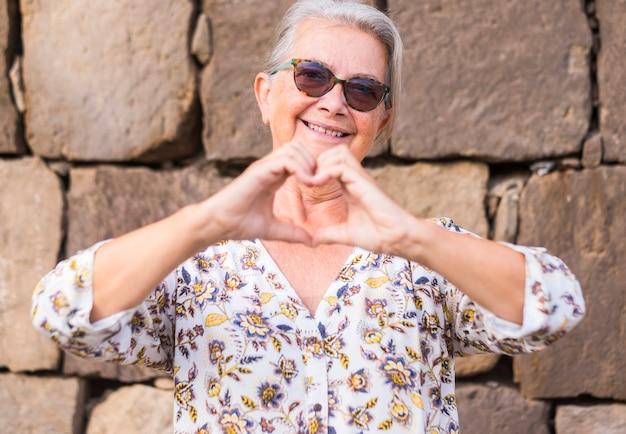 사랑을 표현하는 손으로 심장 모양을 만드는 돌담에 대해 웃고 낭만적인 노인 여성