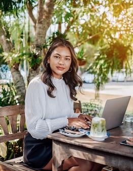 웃고 노트북을 사용하는 아시아 소녀는 음식을 들고 테이블에 앉아 공원 밖에 있는 카메라를 쳐다봅니다.