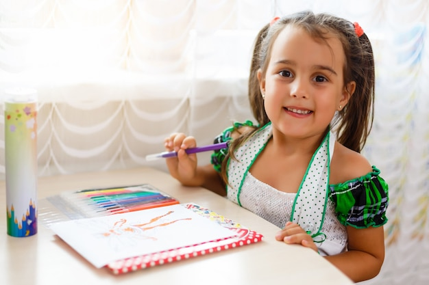 Smiling angel-like beautiful child painting . charming little girl drawing picture for her father, preparing birthday surprise for him.