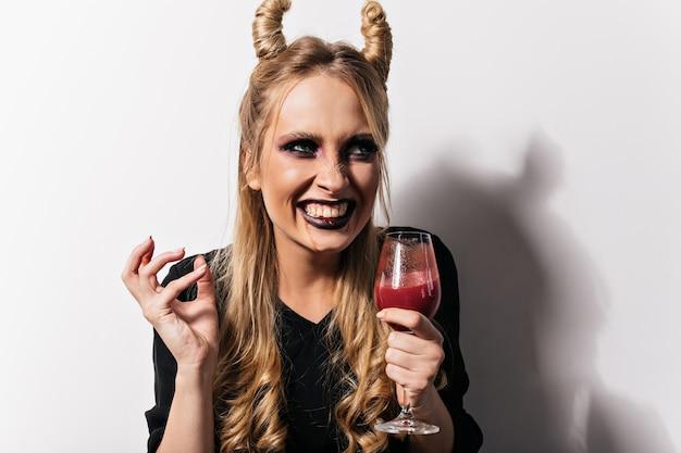 파티를 즐기는 뱀파이어 의상 매력적인 아가씨 미소. 와인 글라스에 가짜 혈액과 웃는 여자의 사진.